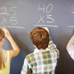 Rear view of children solving math equation on chalkboard