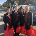 Students Present Winter Appeal Donations Following The Outreach Mass